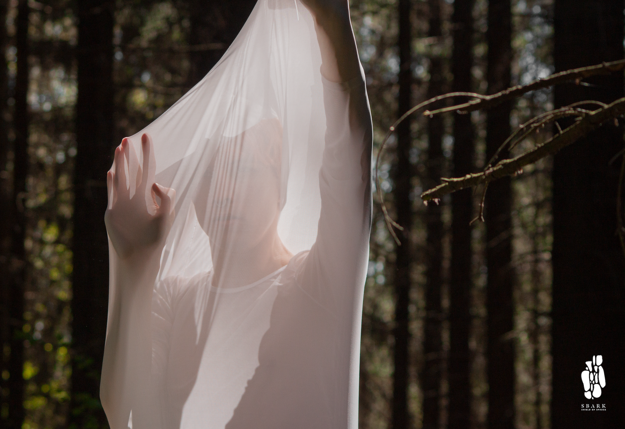 Person behind a white protective fabric in a forest